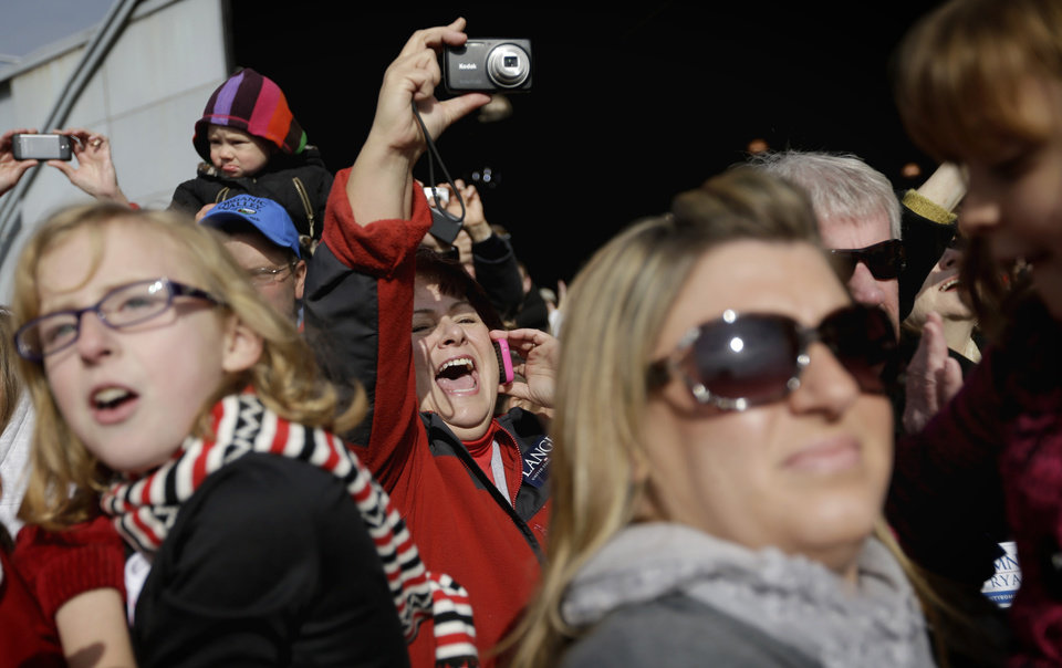 Photo -   Jacqueline Bargman, of Dubuque, Iowa, center, cheers as Republican presidential candidate, former Massachusetts Gov. Mitt Romney, steps out of his plane to speak at a campaign event at Dubuque Regional Airport, before flying to Colorado, Saturday, Nov. 3, 2012, in Dubuque, Iowa. (AP Photo/David Goldman)