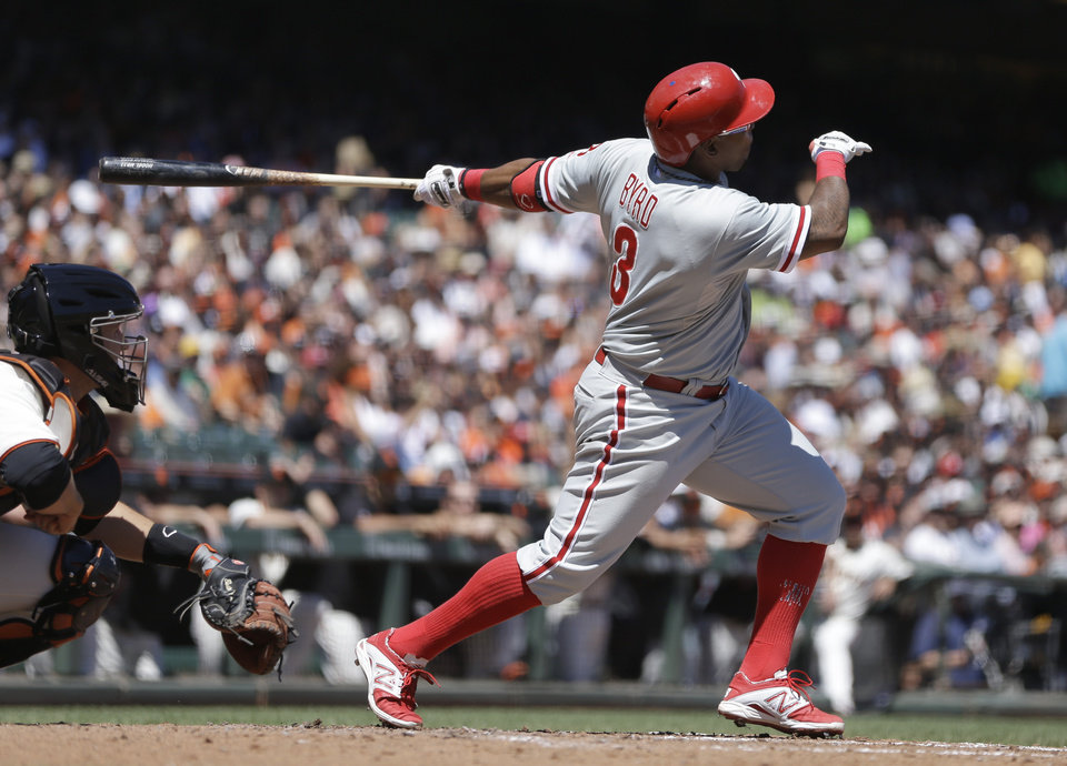Photo - Philadelphia Phillies' Marlon Byrd swings for an RBI-sacrifice fly off San Francisco Giants' Tim Hudson in the third inning of a baseball game Saturday, Aug. 16, 2014, in San Francisco. (AP Photo/Ben Margot)