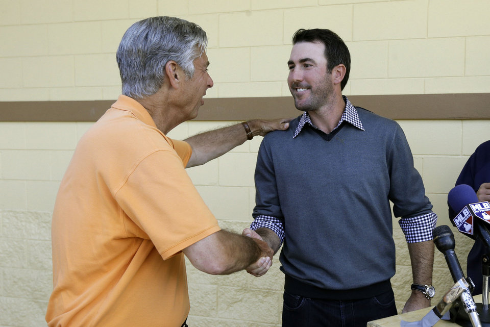 Photo - Detroit Tigers pitcher Justin Verlander, right, shakes hands with team president, CEO and general manager Dave Dombrowski during a news conference after a spring baseball exhibition game on Friday, March 29, 2013, in Lakeland, Fla., where Verlander talked about his new seven-year, $180-million contract. (AP Photo/Carlos Osorio)