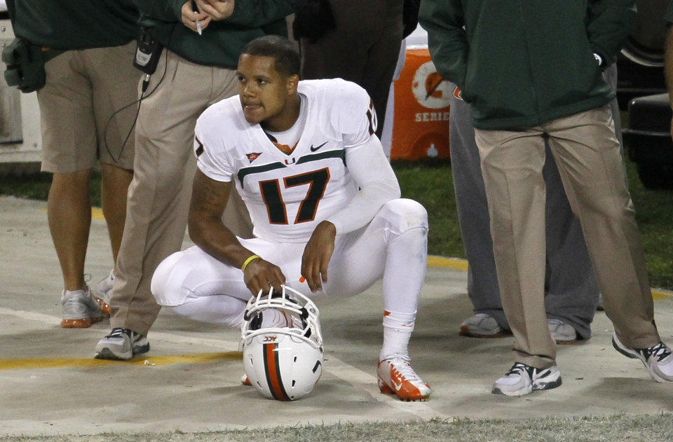 Photo -   Miami quarterback Stephen Morris squats on the sidelines after failing to convert on fourth down during the second half of an NCAA college football game against Notre Dame at Soldier Field on Saturday, Oct. 6, 2012, in Chicago. Notre Dame won 41-3. (AP Photo/Charles Rex Arbogast)