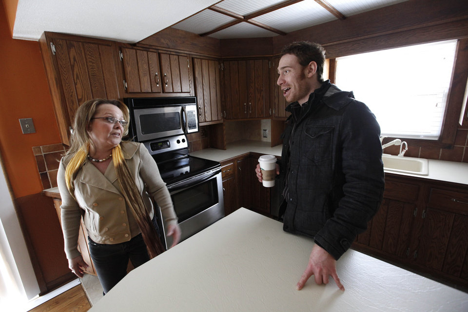 Photo - In this Tuesday, April 2, 2013 photo, real estate agent Michelle Gordon, left, talks with client Michael Weitzman while viewing a home for sale in Grand Rapids, Mich. The American economy and job market are moving in the right direction, just not very quickly. The news Friday, May 3, 2013, that U.S. employers added a solid 165,000 jobs in April and unemployment fell to a four-year low 7.5 percent came as a relief. Fueled by near-record low mortgage rates, the housing market has been bouncing back. New-home sales in March were up 18.5 percent from a year earlier. Sales of previously occupied homes were up 10.3 percent. For the first time in five years, homebuilders started work on more than 1 million homes in March at a seasonally adjusted annual rate. (AP Photo/Paul Sancya)