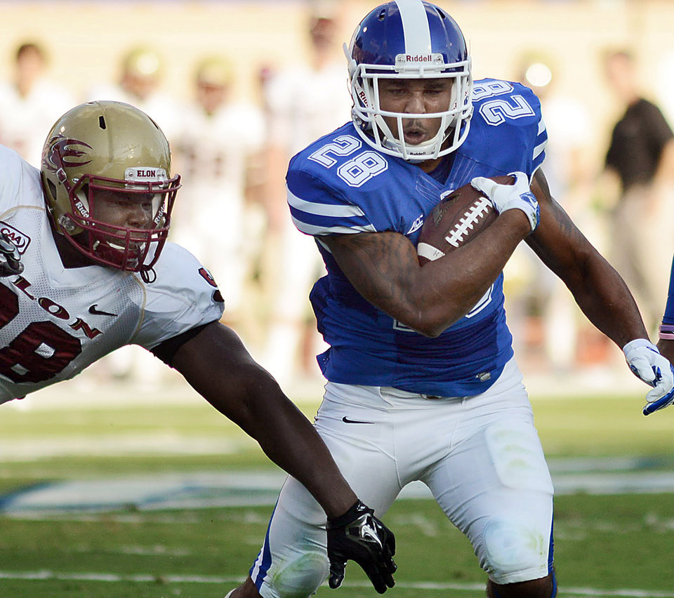 Photo - Duke's Shaquille Powell (28) runs for a first down against  Elon's Chris Jones during the first half of an NCAA college football game Saturday, Aug. 30, 2014, in Durham, N.C. (AP Photo/The Herald-Sun, Bernard Thomas)