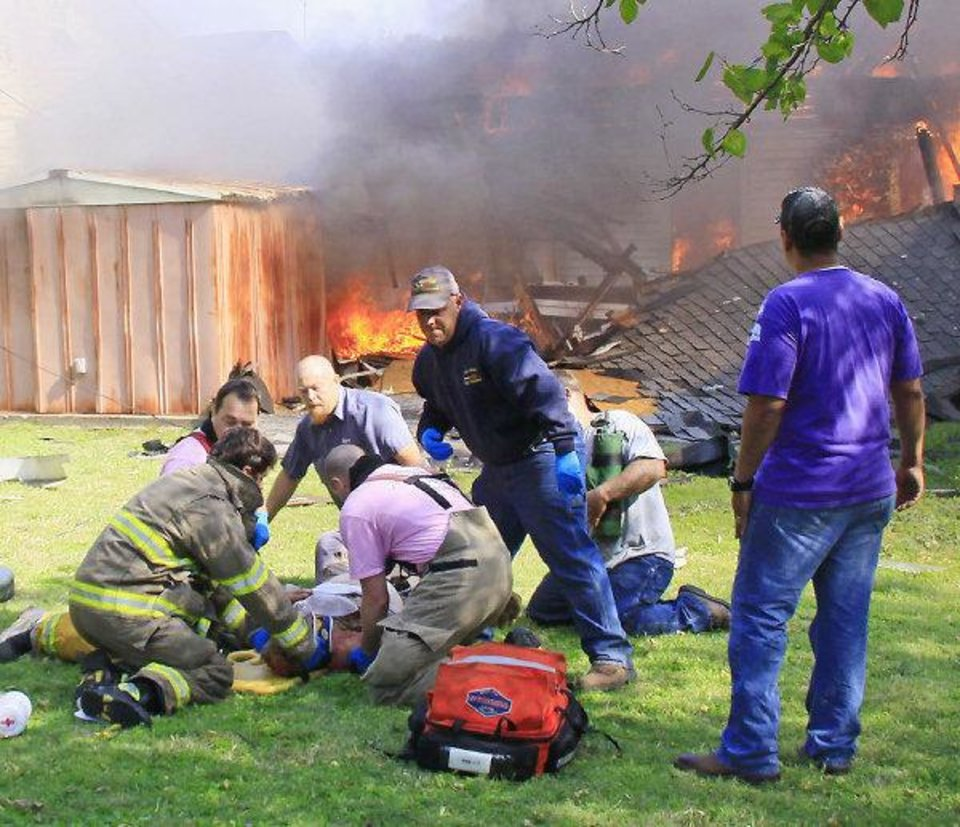 Photo - Rescue workers tend to the needs of Robert Silvy, 84, who was pulled Wednesday from his burning house in Ponca City after it exploded. Silvy died on Thursday. Photo by Rolf Clements / The Ponca City News  ORG XMIT: KOD  Roff Clements - Rolf Clements / The Ponca City N