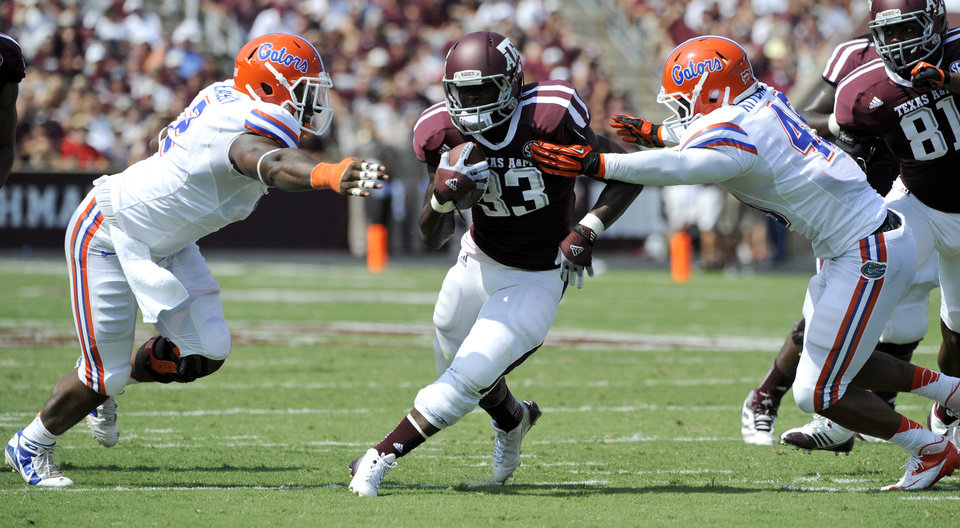 Photo -   Texas A&M running back Christine Michael (33) rushes for a gain as Florida defensive lineman Dominique Easley, left, and linebacker Darrin Kitchens, right, defend during the second quarter of an NCAA college football game, Saturday, Sept. 8, 2012, in College Station, Texas. Texas A&M begins a new era with its first Southeastern Conference game after leaving the Big 12 Conference. (AP Photo/Dave Einsel)