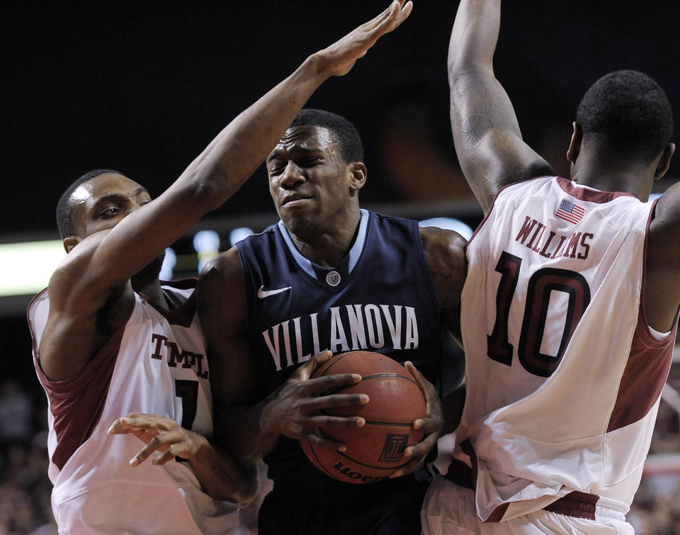 Photo - Villanova's Dylan Ennis (31) drives past Temple's Josh Brown (1) and Mark Williams (10) during the first half of an NCAA college basketball game on Saturday, Feb. 1, 2014, in Philadelphia. (AP Photo/Michael Perez)