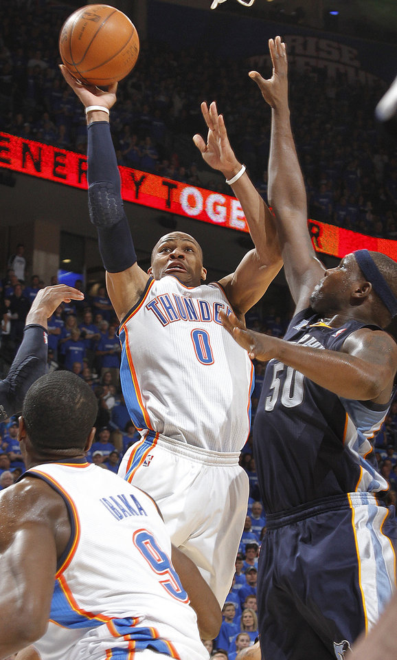 Photo - Oklahoma City's Russell Westbrook (0) drives to the basket past Memphis' Zach Randolph (50) during game one of the Western Conference semifinals between the Memphis Grizzlies and the Oklahoma City Thunder in the NBA basketball playoffs at Oklahoma City Arena in Oklahoma City, Sunday, May 1, 2011. Photo by Chris Landsberger, The Oklahoman