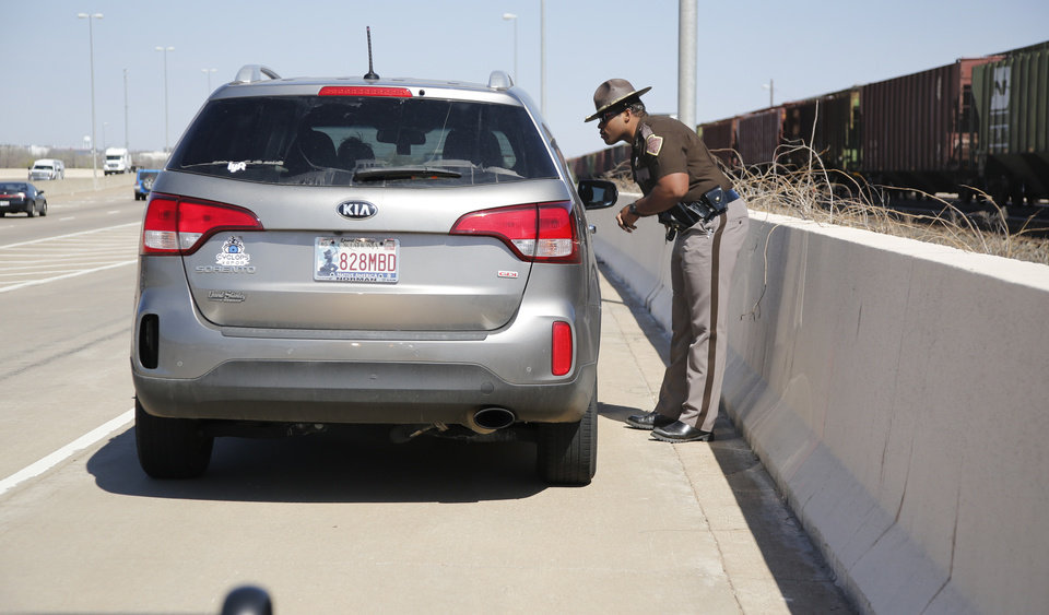 Photo -  Trooper Chantz Jackson with Oklahoma Highway Patrol's Troop A talks to a driver during a traffic stop on Interstate 235 in Oklahoma City. [Photo By Steve Gooch, The Oklahoman]