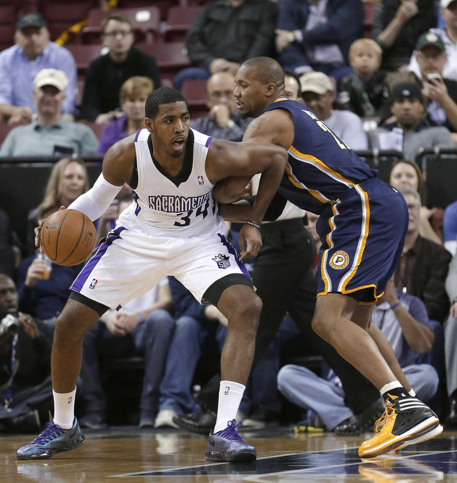 Photo - Sacramento Kings forward Jason Thompson, left, drives against Indiana Pacers forward David West during the first quarter of an NBA basketball game in Sacramento, Calif., Friday, Jan. 24, 2014. (AP Photo/Rich Pedroncelli)