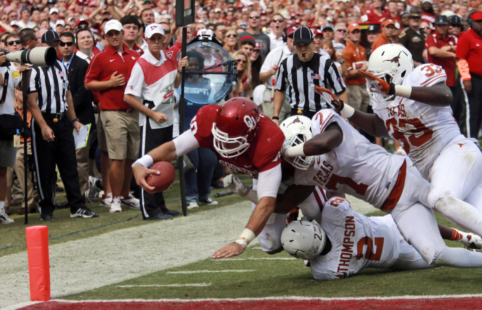 Photo -   Oklahoma quarterback Blake Bell (10) stretches for the gaol line scoring a touchdown against Texas linebacker Steve Edmond (33), defensive back Mykkele Thompson (2) and linebacker Demarco Cobbs (7) during the first half of an NCAA college football game at the Cotton Bowl Saturday, Oct. 13, 2012, in Dallas. (AP Photo/Michael Mulvey)