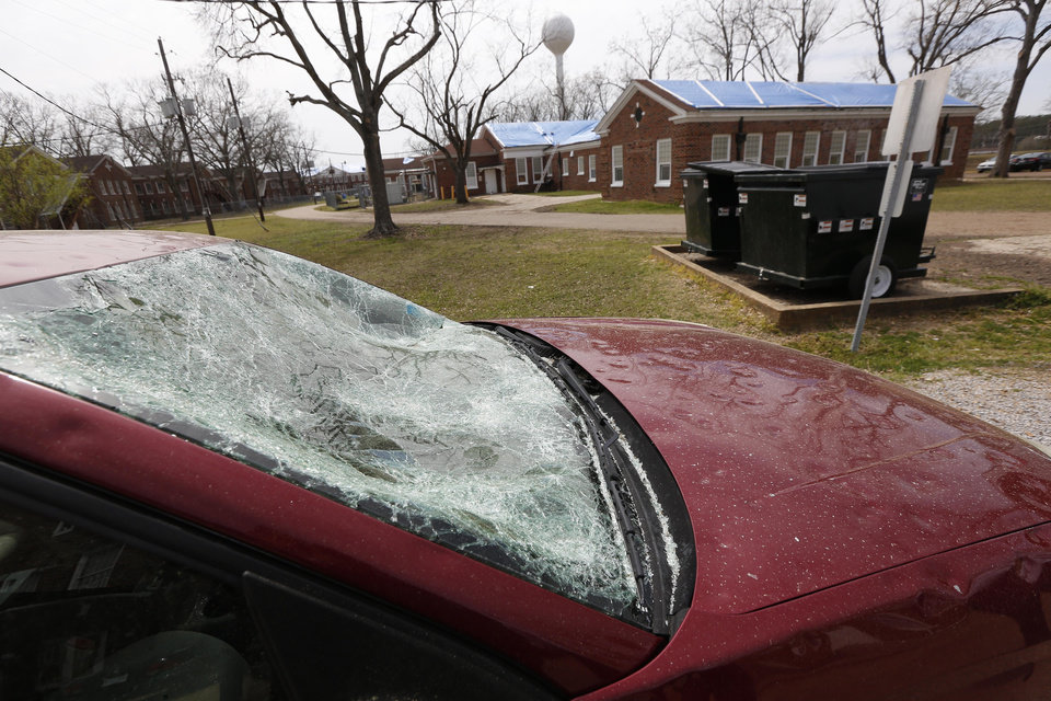 Photo - The windshield of this car belonging to an employee of the Mississippi State Hospital in Whitfield, Miss., awaits towing Thursday, March 21, 2013 as blue tarps go on many of the campus' buildings as workmen race to finish preliminary repairs before another wave of severe weather strikes this weekend. An official estimates this week's hail storm damage could exceed $1 million for the hospital and a nearby facility for people with developmental disabilities.  (AP Photo/Rogelio V. Solis)