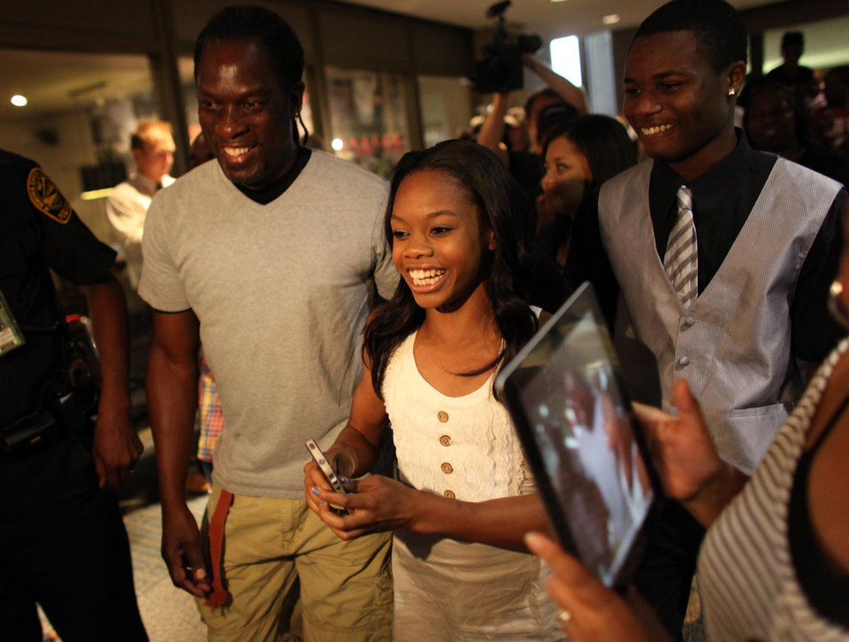 Photo -   Greeted and accompanied by friends and family, 2012 Olympic gymnast and Gold medal winner Gabby Douglas arrives at the Norfolk, Va. Airport on Thursday evening, Aug. 16, 2012, on a visit to hometown of Virginia Beach, Va. (AP Photo/The Virginian-Pilot, Ross Taylor)