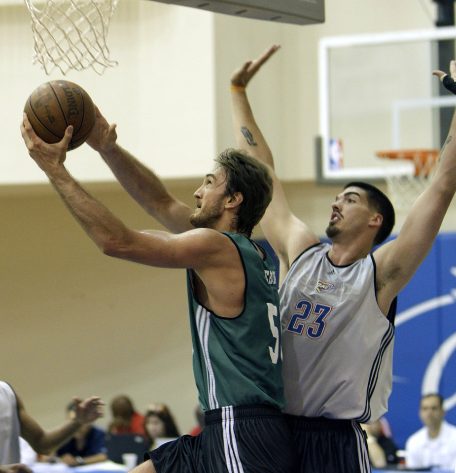 Photo - Boston's Semih Erden, left, gets off a shot in front of Oklahoma City's Byron Mullens during Monday's summer league game. AP PHOTO
