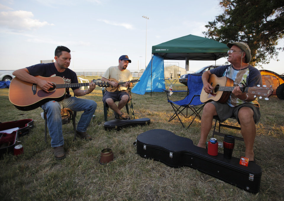 Ross Johnson, Jeff Clanton, and Travis Williams play music near their camp during the Woody Guthrie Folk Festival in Okemah, Okla., Thursday, July 12, 2012.  Photo by Garett Fisbeck, The Oklahoman
