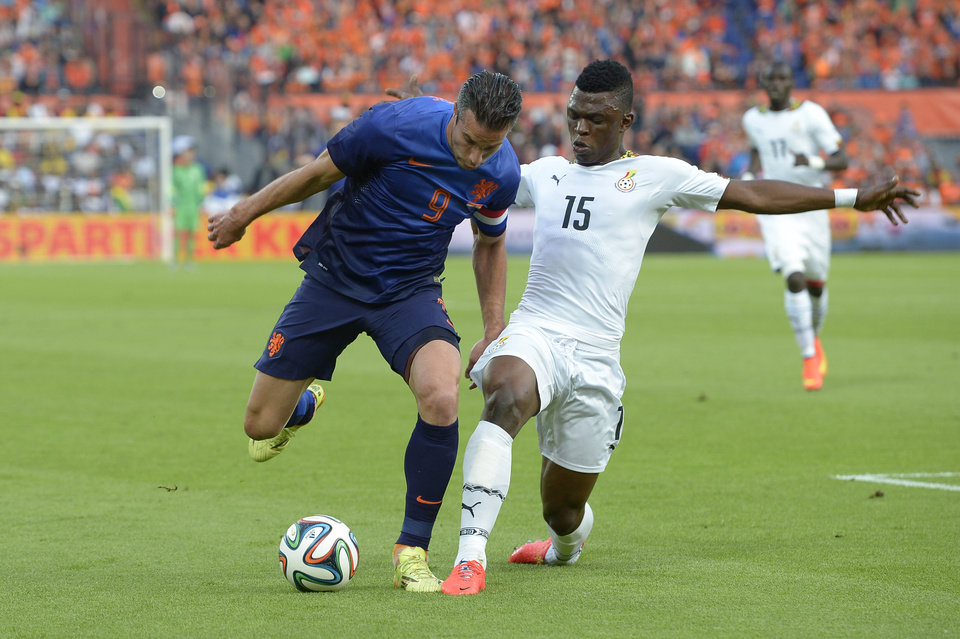 Photo - Netherlands Robin van Persie, left, fights for the ball with Sumaila Rashid from Ghana, during the international friendly soccer match between The Netherlands and Ghana at De Kuip stadium in Rotterdam, Netherlands, Saturday, May 31, 2014. (AP photo/Ermindo Armino)