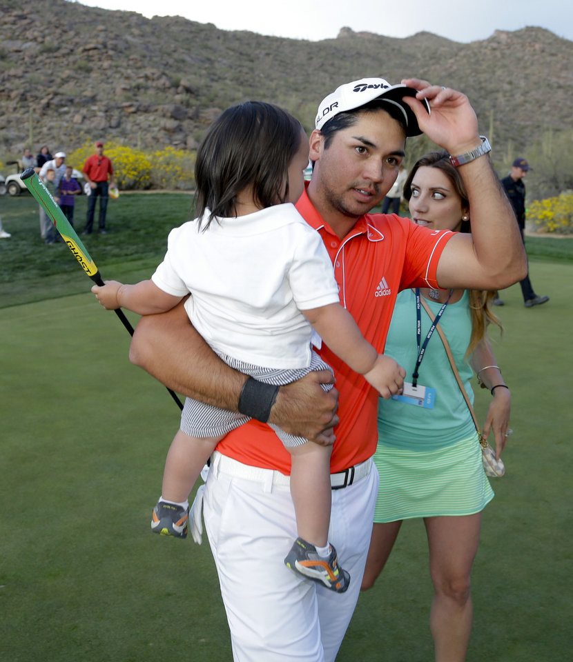 Photo - Jason Day, of Australia, holds his son Dash, as he walk off the green with his wife, Ellie, after winning his championship match against Victor Dubuisson, of France, during the Match Play Championship golf tournament on Sunday, Feb. 23, 2014, in Marana, Ariz. (AP Photo/Ted S. Warren)