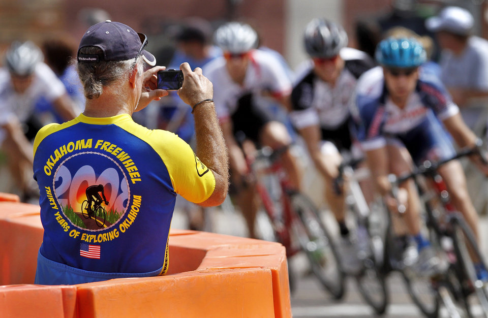 Photo - Kim Hynek takes pictures as cyclists turn the corner at 8th  and North Broadway during the Oklahoma City ProAm Classic, with races scheduled from 11 a.m. to 9 p.m. in Automobile Alley,  just north of downtown Oklahoma City on Saturday, June 2,  2012.  Hynek, of Choctaw,  is a member  of the Oklahoma Bicycle Society.  Photo by Jim Beckel, The Oklahoman