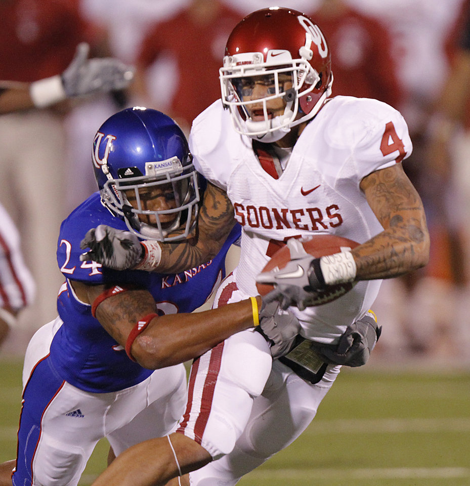 Photo - Oklahoma's Kenny Stills (4) makes a reception in front of Kansas' Bradley McDougald (24) during the college football game between the University of Oklahoma Sooners (OU) and the University of Kansas Jayhawks (KU) on Saturday, Oct. 15, 2011. in Lawrence, Kan. Photo by Chris Landsberger, The Oklahoman