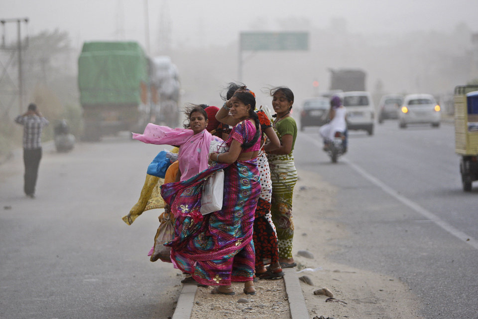 Wind from a dust storm blows the hair and clothing of Indian women waiting to cross a road in Jammu, India, Saturday, May 11,2013. (AP Photo/Channi Anand)