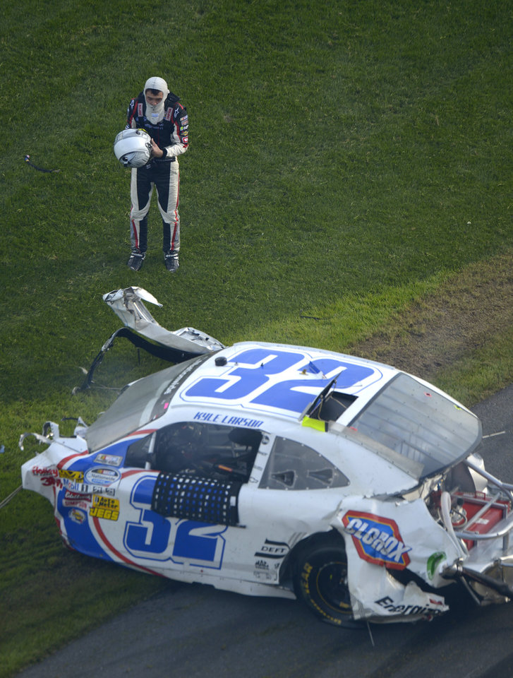 Driver Kyle Larson stands outside his car, missing the engine, after hitting the wall and safety fence along the front grandstands on the final lap of a NASCAR Nationwide Series auto race at Daytona International Speedway in Daytona Beach, Fla., Saturday, Feb. 23, 2013.(AP Photo/Phelan M. Ebenhack)