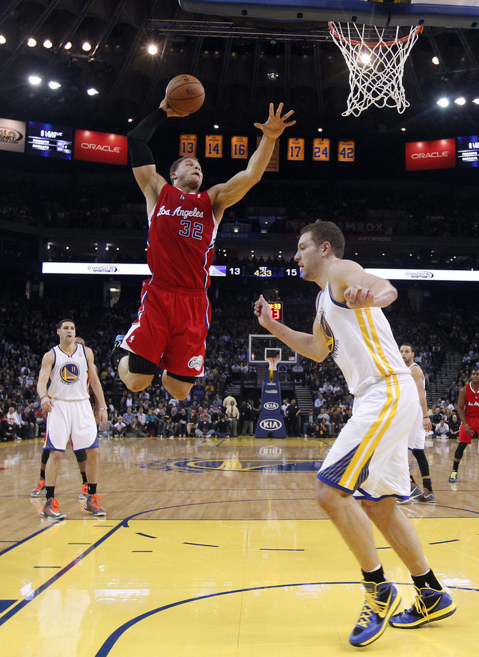 Los Angeles Clippers' Blake Griffin (32) goes up for a dunk next to Golden State Warriors' David Lee, right, as Klay Thompson (11) watches during the first half of an NBA basketball game in Oakland, Calif., Monday, Jan. 21, 2013. (AP Photo/Marcio Jose Sanchez)