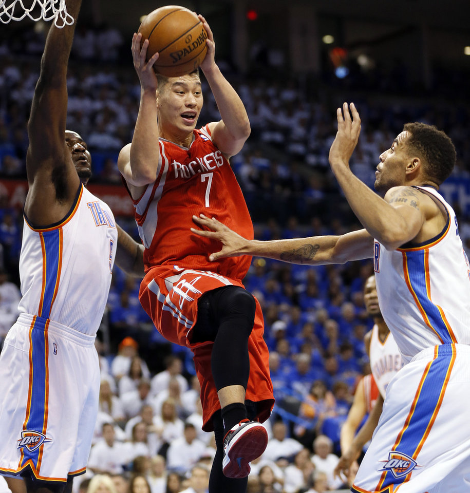 Photo - Houston's Jeremy Lin (7) passes away from Oklahoma City's Kendrick Perkins (5) and Thabo Sefolosha (2) during Game 2 in the first round of the NBA playoffs between the Oklahoma City Thunder and the Houston Rockets at Chesapeake Energy Arena in Oklahoma City, Wednesday, April 24, 2013. Photo by Nate Billings, The Oklahoman