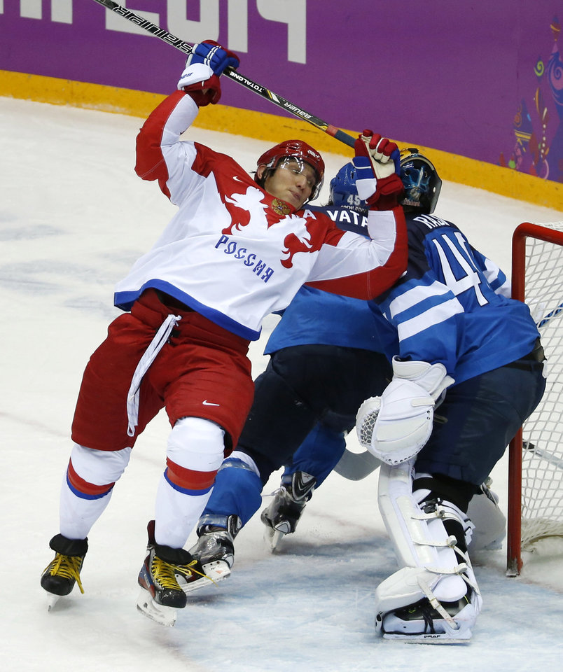 Photo - Russia forward Alexander Ovechkin, left, loses his balance while trying to score against Finland in the second period of a men's quarterfinal ice hockey game at the 2014 Winter Olympics, Wednesday, Feb. 19, 2014, in Sochi, Russia. (AP Photo/Mark Humphrey)
