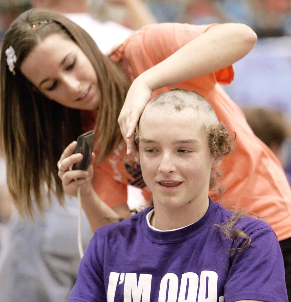 Photo - Ally Freeman buzzes the hair off of Tyler Segerstron during the final assembly of Double Wolf Dare Week at Edmond Santa Fe High School in March.  PHOTO BY PAUL HELLSTERN, OKLAHOMAN ARCHIVE