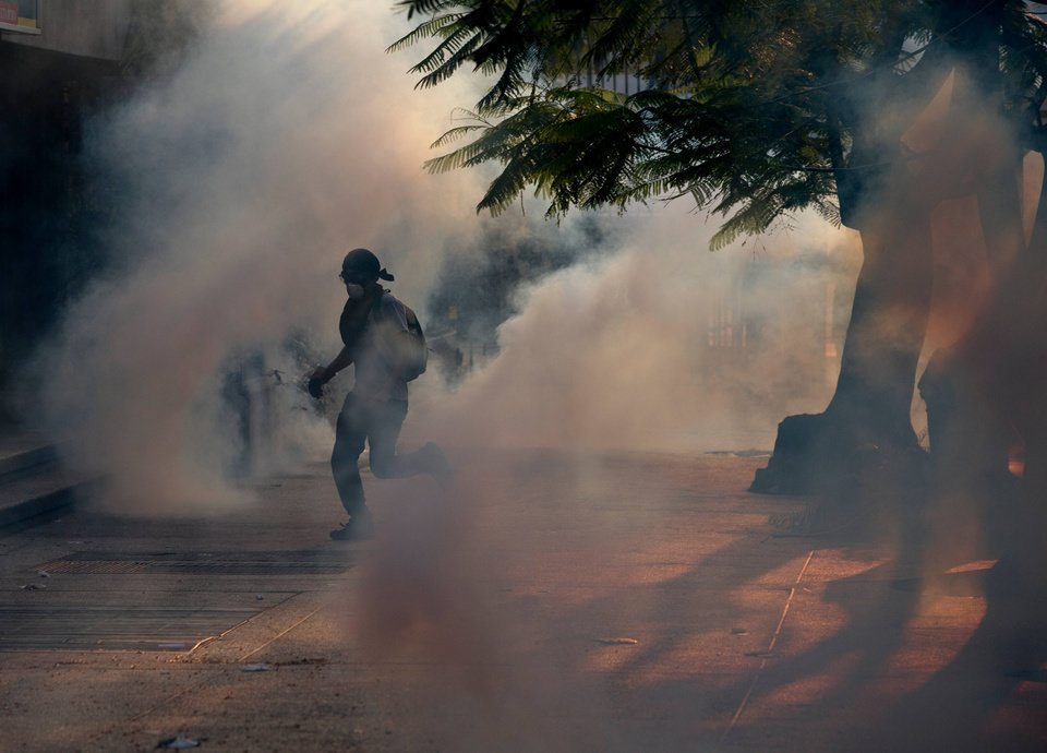 Photo - A demonstrator take cover from tear gas fired by Bolivarian National police during clashes with anti-government protesters in Caracas,Venezuela, Saturday, March 8, 2014. The Venezuelan government and opposition appear to have reached a stalemate, in which street protests continue almost daily while the opposition sits out a peace process it calls farcical. (AP Photo/Fernando Llano)