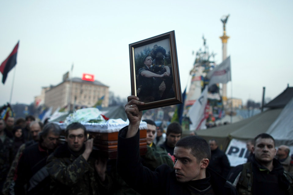 Photo - A man carries a photo of an anti-government protester killed in clashes with the police, during a funeral procession at Independence Square in Kiev, Ukraine, Friday, Feb. 21, 2014. In a day that could significantly shift Ukraine's political destiny, opposition leaders signed a deal Friday with the country's beleaguered president that calls for early elections, a new constitution and a new unity government. (AP Photo/ Marko Drobnjakovic)