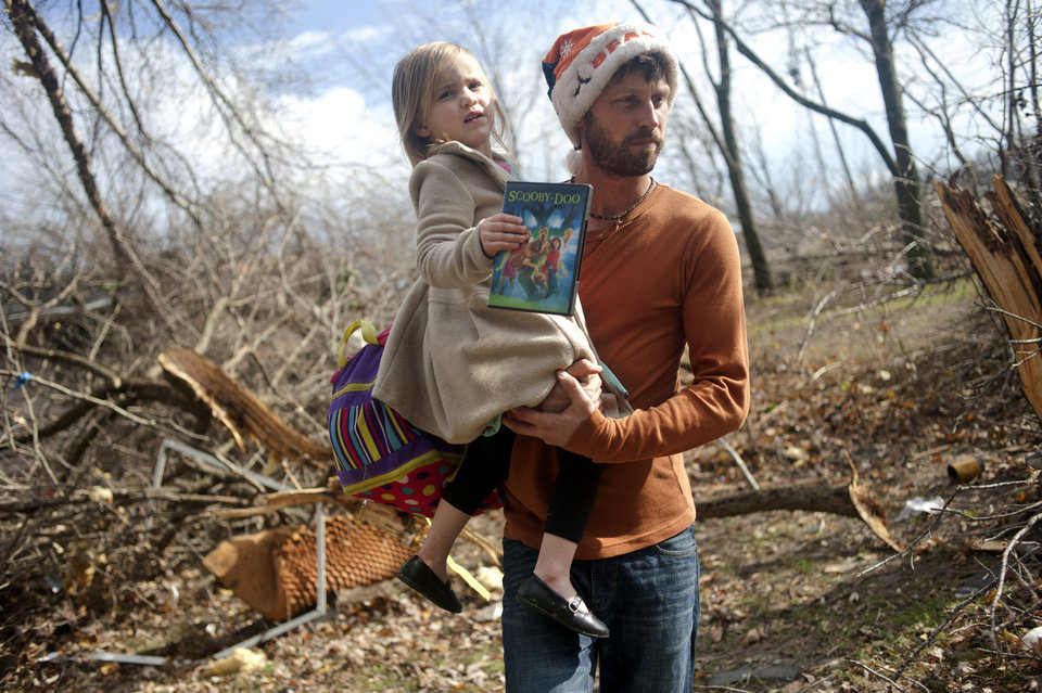 Photo - East Peoria resident Billy Vestal evacuates with his daughter, Lillian Vestal, 3, after a tornado damaged the area near Chestnut Road in East Peoria, Il.,Sunday, Nov. 17, 2013. Intense thunderstorms and tornadoes swept across the Midwest on Sunday, causing extensive damage in several central Illinois communities while sending people to their basements for shelter. (AP Photo/Journal Star, Justin Wan) MANDATORY CREDIT
