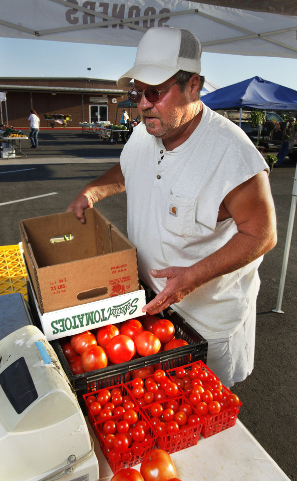 Photo - Terry Nixon with Elam Produce, of Purcell, unloads tomatoes Wednesday at the Norman Farm Market. PHOTO BY STEVE SISNEY, THE OKLAHOMAN  STEVE SISNEY