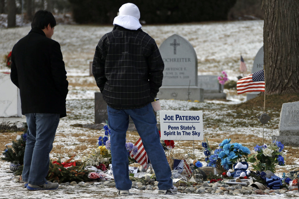 Photo - Penn State students Dan Hamm, left, a freshman from Williamsport, Pa., and Nick Bucci, a freshman from Dayton, Md., visit the grave of former Penn State head football coach Joe Paterno in State College, Pa. Supporters of Paterno are marking the 1-year anniversary of his death with a candlelight vigil Tuesday night.  (AP Photo/Gene J. Puskar)
