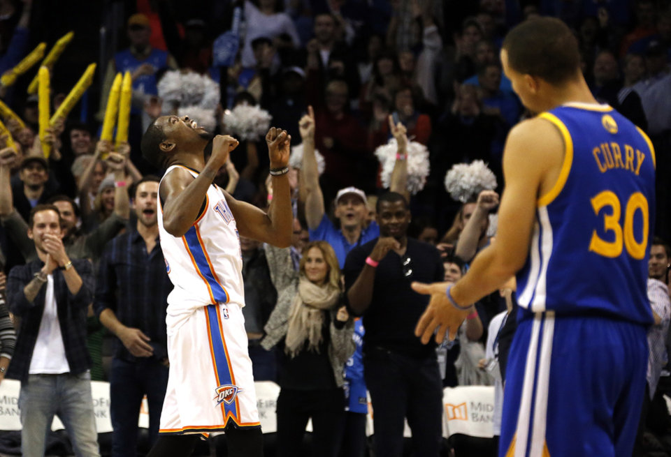 Photo - Oklahoma City's Kevin Durant (35) celebrates the the Thunder's overtime win as Golden State's Stephen Curry (30) looks on following the NBA game between the Oklahoma City Thunder and the Golden State Warriors at the Chesapeake Energy Arena, Friday, Nov. 29, 2013. Photo by Sarah Phipps, The Oklahoman