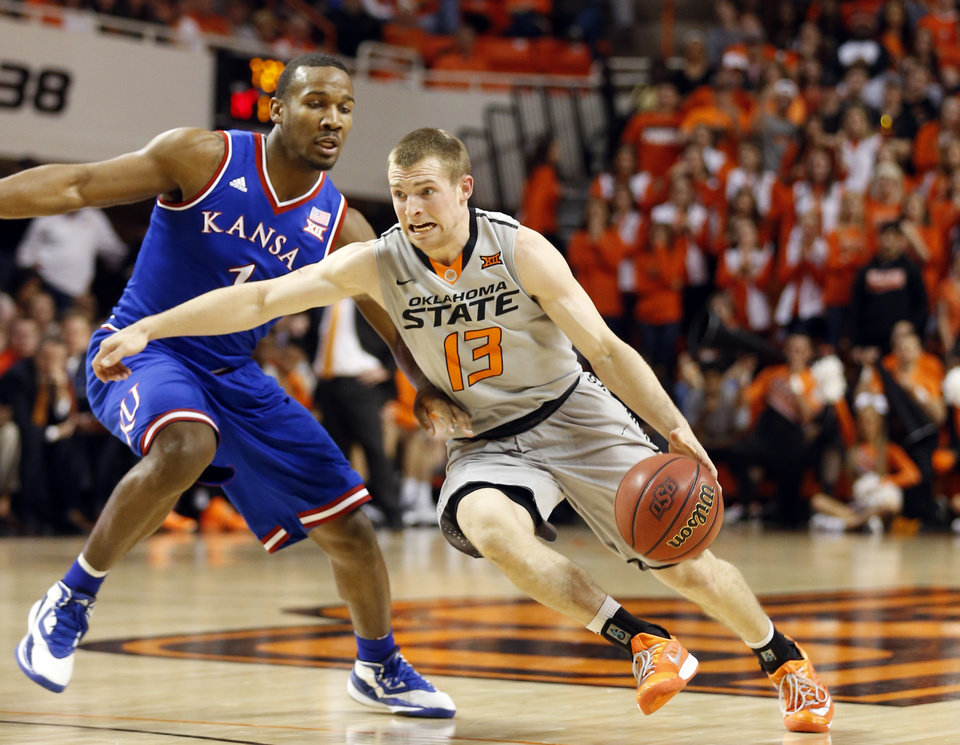 Photo - Oklahoma State's Phil Forte III (13) drives to the basket as Kansas' Wayne Selden Jr. (1) defends during the men's college basketball game between Oklahoma State University and the University of Kansas at Gallagher-Iba Arena in Stillwater, Okla.,  Saturday, Feb. 7, 2015. OSU won 67-62. Photo by Sarah Phipps, The Oklahoman