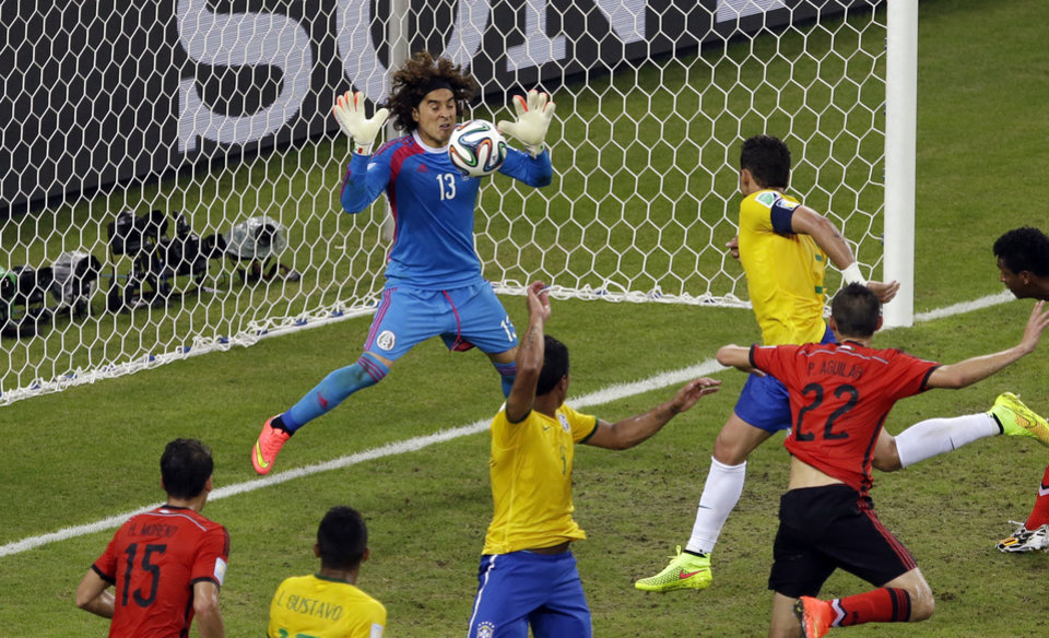 Photo - Mexico's goalkeeper Guillermo Ochoa, left,  saves a header by Brazil's Thiago Silva  during the group A World Cup soccer match between Brazil and Mexico at the Arena Castelao in Fortaleza, Brazil, Tuesday, June 17, 2014.  (AP Photo/Themba Hadebe)