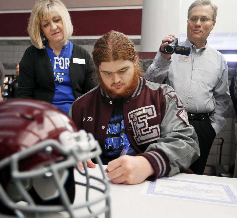 Photo - Jordan Weltzheimer signs to play football with Air Force as his parents, Marie Weltzheimer and Ron Weltzheimer, watch during the college signing day ceremony for student athletes at Edmond Memorial High School in Edmond, Okla., Wednesday, Feb. 5, 2014. Photo by Nate Billings, The Oklahoman