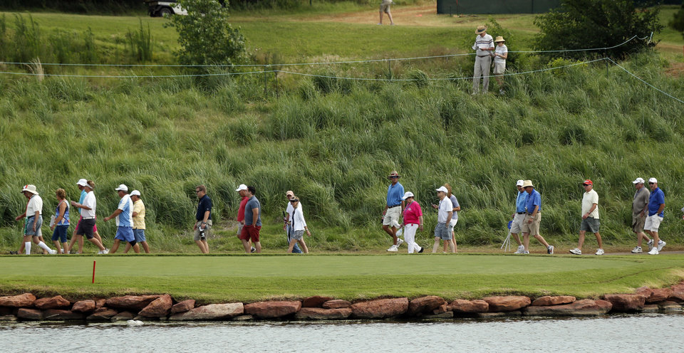 Photo - Fans walk near the17th green during the first round of the U.S. Senior Open Championship golf tournament at Oak Tree National in Edmond, Okla. on Thursday, July 10, 2014. Photo by Steve Sisney, The Oklahoman