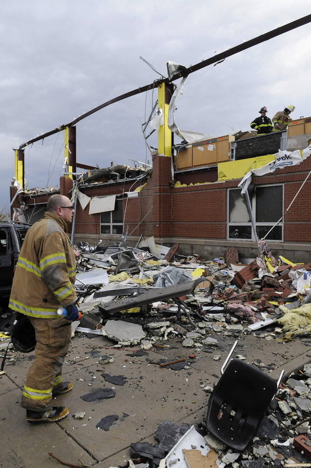 Firefighters with the Jeffersonville, Ind., fire department coordinate a search of the Henryville Middle School following severe storms Friday, March 2, 2012, in Henryville, Ind. Tornadoes ripped across several small southern Indiana towns on Friday, killing at least three people and leaving behind miles of flattened devastation along the border with Kentucky. (AP Photo/Timothy D. Easley) ORG XMIT: KYTE106