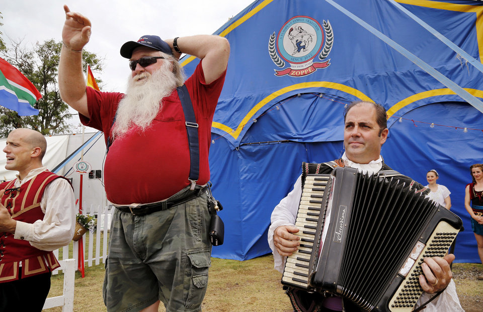 Photo - After requesting a member of the Zoppe Italian Family Circus to play a song on his accordion, Bob Moore of Piedmont, was pulled from the crowd and invited to stand on a drum to sing the song while accordionist Jay Walther provided the tune. After performing a few tunes to warm up the crowd, the curtains of the tent were opened and the circus performers entertained a crowd of about 500 fairgoers under the big top tent in the Centennial Plaza at the Oklahoma State Fair on Wednesday,  Sep. 18, 2013. Photo  by Jim Beckel, The Oklahoman.