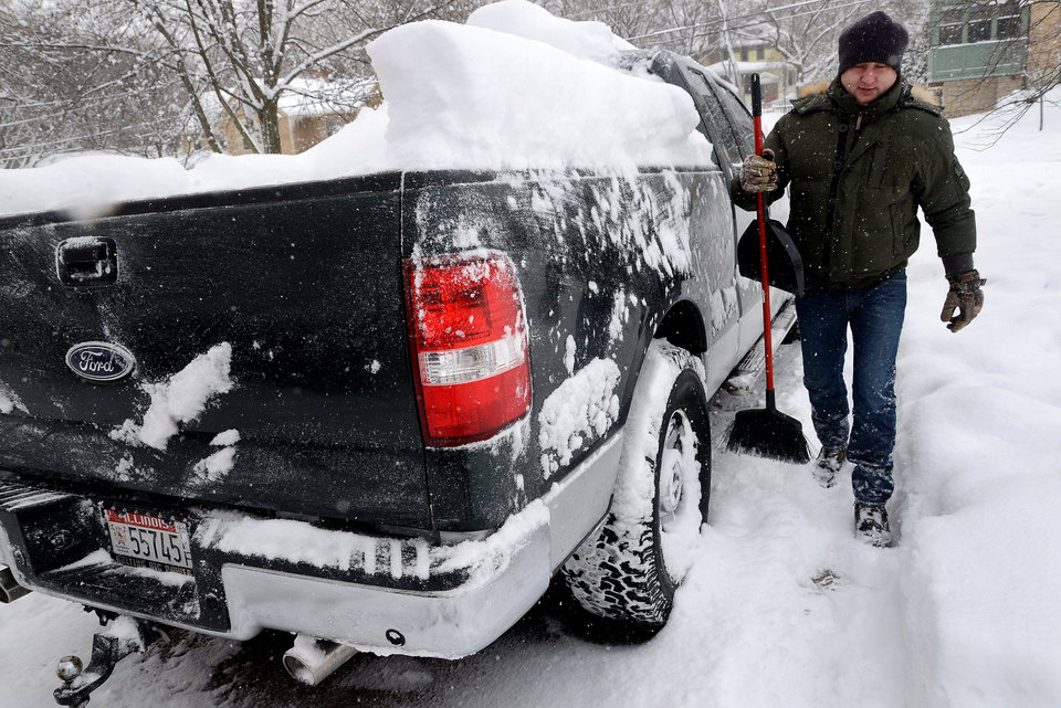 Photo - David Paluch brushes off snow from his truck in front of his home in Barrington, Ill., Thursday, Jan. 2, 2014. The New Year's Day snow storm stretched into Thursday for parts of Illinois, bringing double-digit snow totals to the suburbs of Chicago. (AP Photo/Daily Herald, Bob Chwedyk) MANDATORY CREDIT; MAGS OUT;  TV OUT