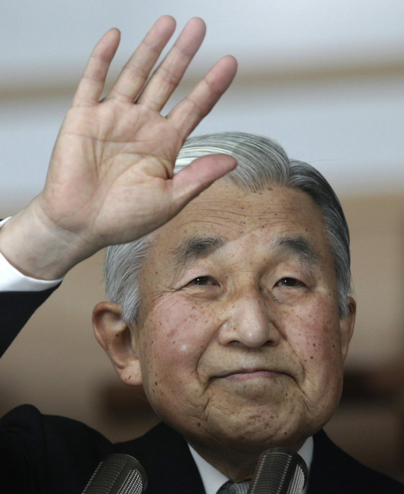 Japan\'s Emperor Akihito waves to a crowd of well-wishers through the bulletproof glass of a balcony, during a morning appearance to mark his 79th birthday, at the Imperial Palace in Tokyo Sunday, Dec. 23, 2012. (AP Photo/Shizuo Kambayashi)
