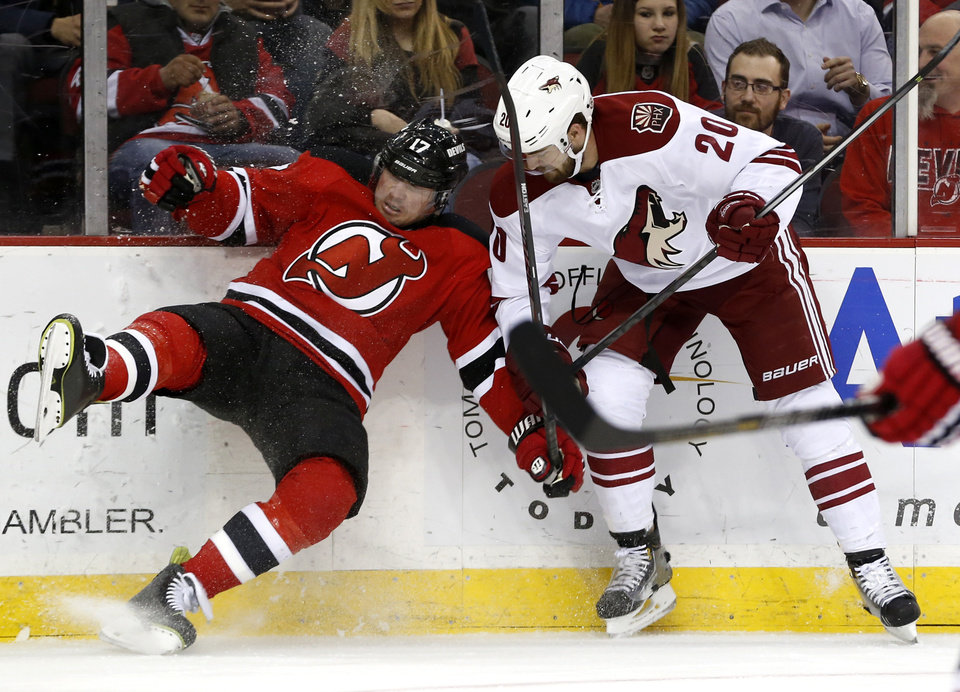 Photo - New Jersey Devils right wing Michael Ryder, left, falls to the ice while challenging Phoenix Coyotes defenseman Chris Summers for the puck during the second period of an NHL hockey game, Thursday, March 27, 2014, in Newark, N.J. (AP Photo/Julio Cortez)