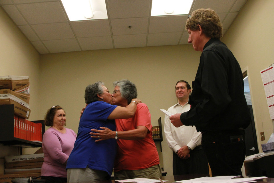 Photo - Catherine Martinez and Linda Montoya kiss as Dona Ana County employee and Reverend Jess C. Williams marries them at the Dona Ana County Clerk's Office in Las Cruces, New Mexico, Wednesday, Aug. 21, 2013. More than 40 same-sex couples obtained their marriage licenses after the county clerk announced the county would be the first in New Mexico to marry same-sex couples. (AP Photo/Juan Carlos Llorca)
