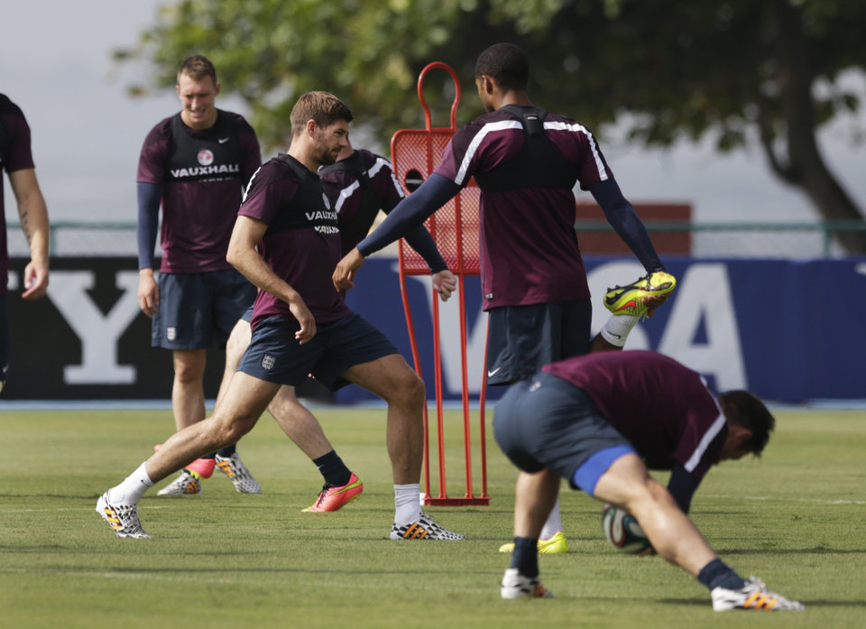 Photo - England national soccer team players captain Steven Gerrard, center left, Glen Johnson, second right, and Frank Lampard, right, stretch during a squad training session for the 2014 soccer World Cup at the Urca military base in Rio de Janeiro, Brazil, Wednesday, June 11, 2014.  The England soccer team are staying in Rio de Janeiro as their base city for the 2014 soccer World Cup.  (AP Photo/Matt Dunham)