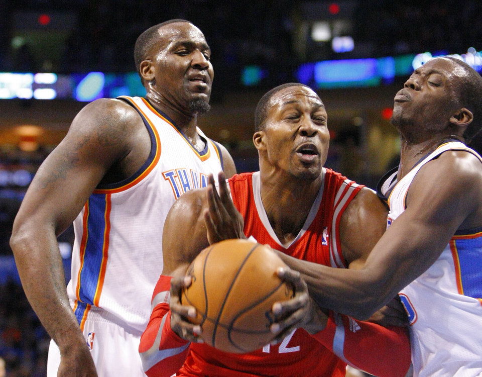 Photo - Houston Rockets center Dwight Howard goes to the basket between Oklahoma City Thunder's Kendrick Perkins, left, and Reggie Jackson, right, during the first quarter of an NBA basketball game, Sunday, Dec. 29, 2013, in Oklahoma City. (AP Photo/Alonzo Adams)