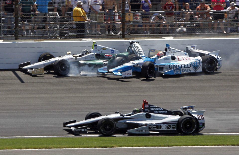 Photo - James Hinchcliffe (27) and Ed Carpenter crash in the first turn during the 98th running of the Indianapolis 500 IndyCar auto race at the Indianapolis Motor Speedway in Indianapolis, Sunday, May 25, 2014. Kurt Busch, bottom, avoids the crash. (AP Photo/Kirk DeBrunner)