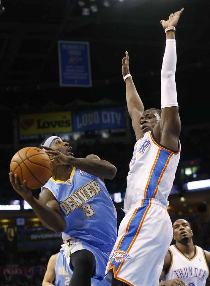 Photo - Denver Nuggets guard Ty Lawson (3) shoots as Oklahoma City Thunder guard Reggie Jackson (15) defends in the first quarter of an NBA basketball game in Oklahoma City, Monday, March 24, 2014. (AP Photo/Sue Ogrocki)