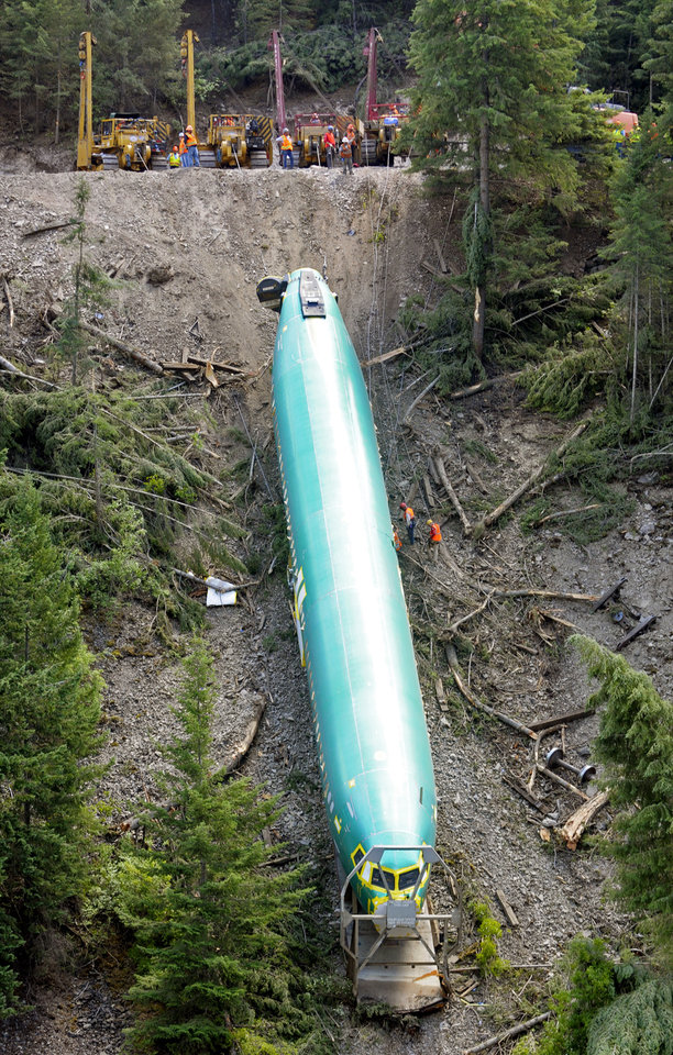 Photo - A work crew pulls a Boeing 737 fuselage up a bank of the Clark Fork River near Alberton, Mont., Tuesday, July 8, 2014, as efforts to retrieve three fuselages that tumbled down the embankment following a derailment last week continued. The fuselage was the second of three in or near the river to be recovered. (AP Photo/The Missoulian, Tom Bauer)