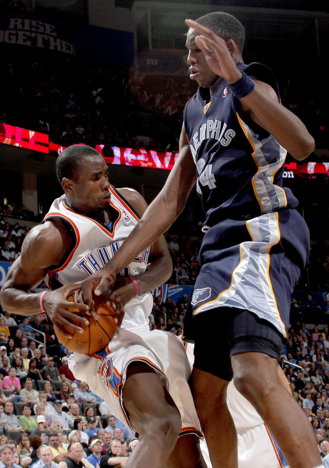 Oklahoma City's Serge Ibaka grabs the ball beside Hasheem Thabeet of Memphis during the NBA basketball game between the Oklahoma City Thunder and the Memphis Grizzlies at the Ford Center in Oklahoma City on Wednesday, April 14, 2010. 
