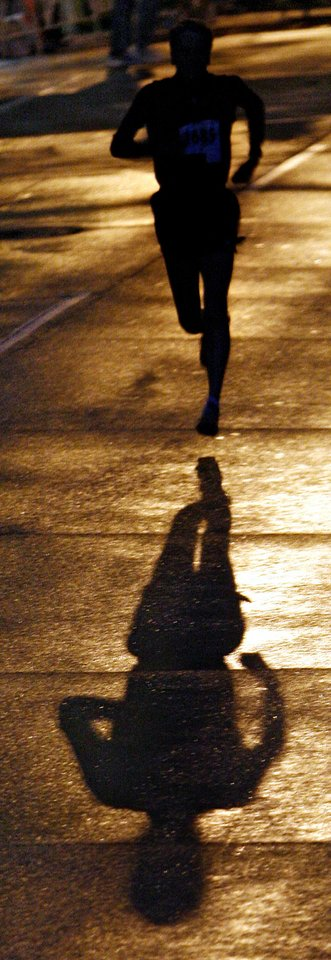 A marathon participant cast a shadow on the street while warming up before the eighth annual Oklahoma City Memorial Marathon on Sunday , April 27, 2008, in Oklahoma City, Okla.   PHOTO BY CHRIS LANDSBERGER   ORG XMIT: KOD